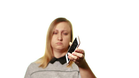 The concept of a broken gadget. Frustrated and tired woman shows a smartphone Live Action