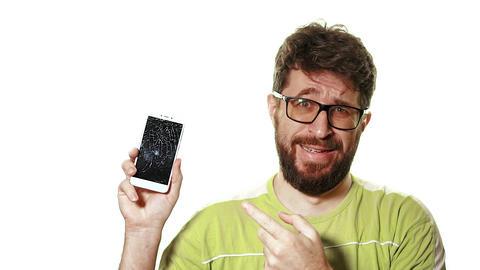 The concept of a broken gadget. Bearded upset man holding a smartphone broken Live Action