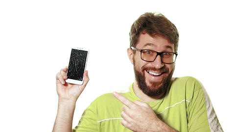 The concept of a broken gadget. A bearded man shows the smartphone with a broken Live Action
