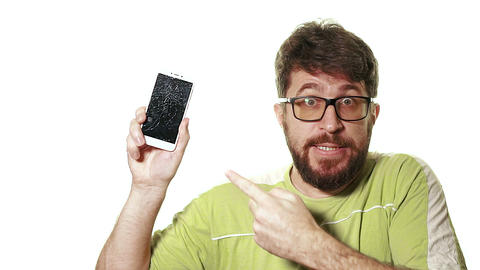 The concept of a broken gadget. Bearded angry man showing broken smartphone Live Action