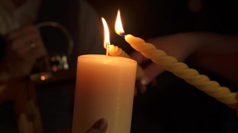 Candle light another candle in their hands Footage