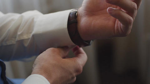 Close-up of a successful man is putting on a wristwatch. Men's hand with a watch Live Action