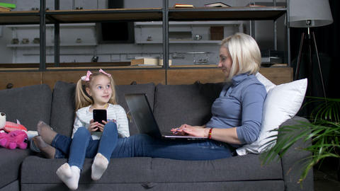 Little girl and mom spending time using devices Live Action