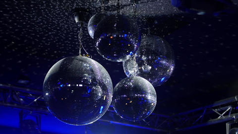 Rotating Mirrorballs in a club reflecting blue light - close up shot Live Action