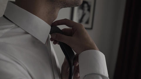 Elegant business man in white shirt correcting his tie and buttoning his suit Live Action