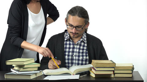 Man Sitting At Table Studying Hard, Discussing With Woman How To Solve The Task stock footage