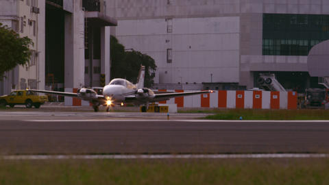 Static shot of plane taxis on tarmac in front of buildings at Jacarepaguá Airpo Footage