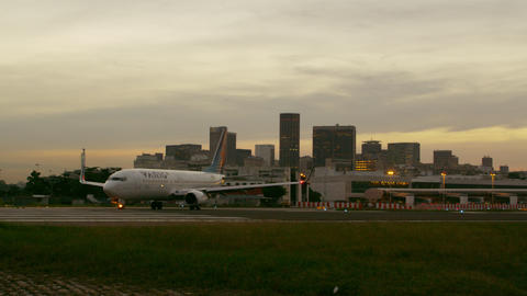 Plane taxis on runway with buildings of Rio de Janeiro in background Footage