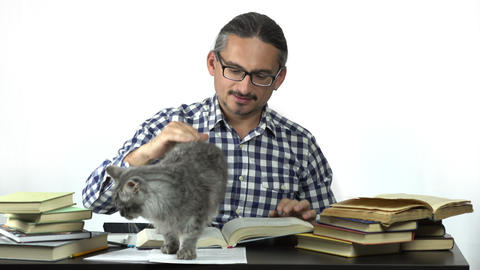 man sitting at table studying with his cat Live Action