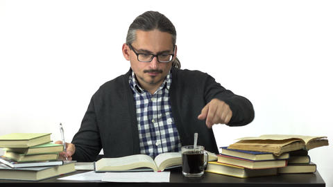 man sitting at table studying and stirring coffee Footage