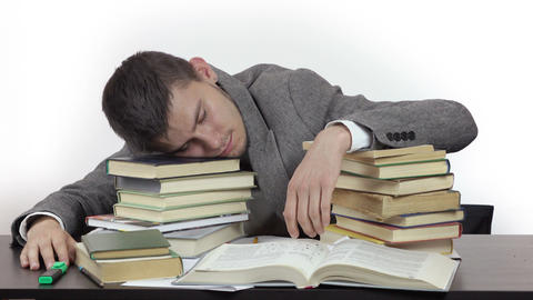 young tired student is sleeping at table surrounded by books Footage