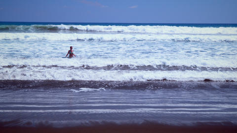 Long distance static shot of woman playing in the water near the beach Footage