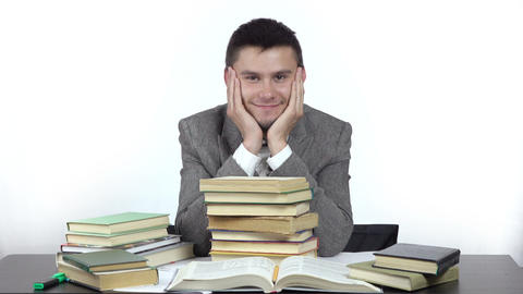 young smiling student is sitting at table surrounded by books Footage