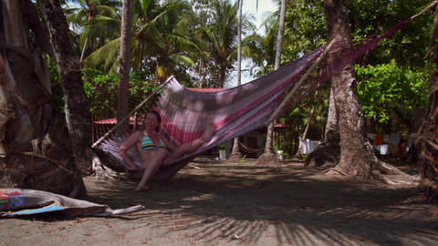 Woman sits in beach hammock near beach house Footage