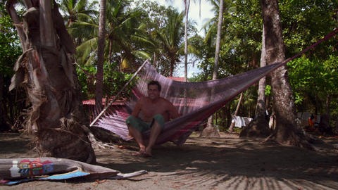 Man sits in beach hammock near beach house Footage