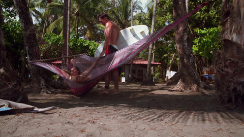 Man holding surfboard kisses woman swinging in hammock Footage