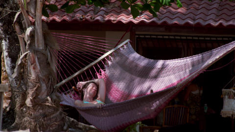Bikini-clad woman swings in hammock at beachfront house Footage