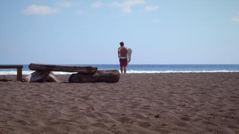 Male surfer steps off driftwood, runs towards ocean Footage
