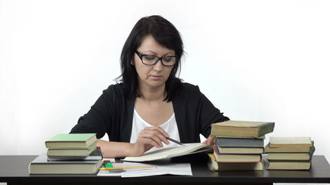 attractive woman sitting at table studying and writing in notebook Footage
