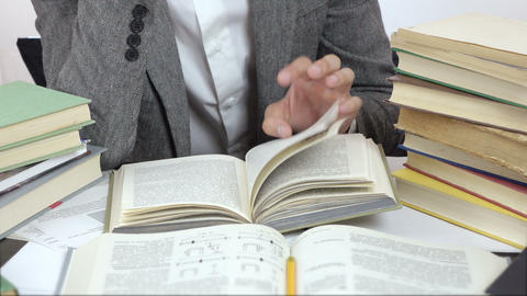 close up video of reading student, surrounded by books Footage
