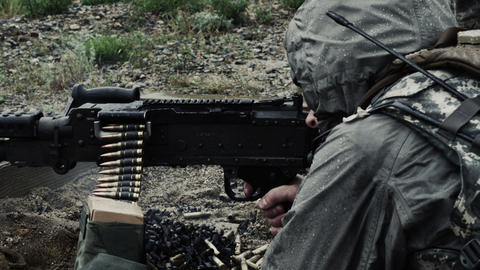 Shot of a soldier firing a belt-fed machine gun from a sitting position Footage