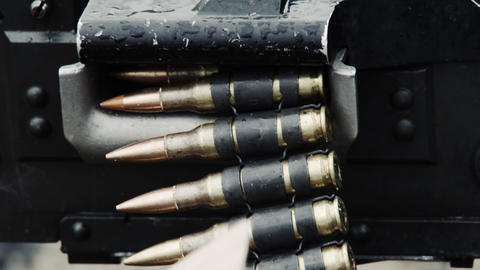 Close-up of a chain of bullets going through a belt-fed machine gun Footage