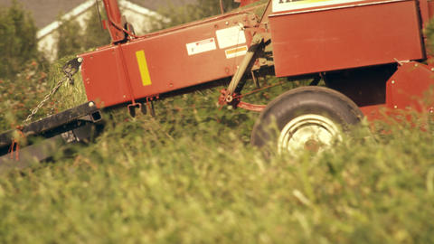 Shot of a square hay baler going around the farm as it turns piles of hay into b Footage