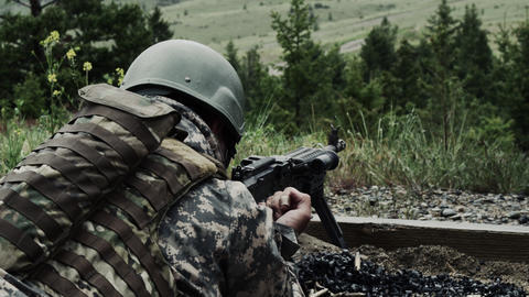 Soldier with a belt-fed machine gun. He pulls back on a lever on the firearm and Footage