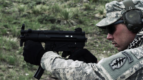 Soldier shooting a sub machine gun, first single shot then full auto Footage