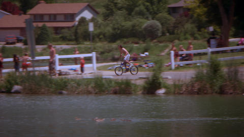 Slow motion, panning shot of a boy jumping his bike into a lake Footage