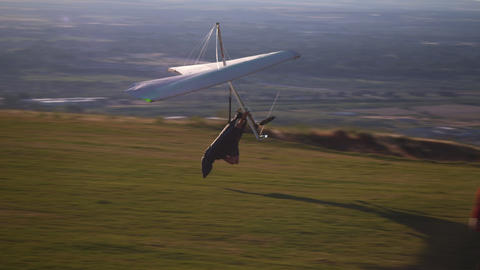 Shot of hang glider slowing and coming to a stop on top of a hill Footage