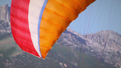 Shot of paraglider's parachutes followed the paragliders themselves standing on  Footage