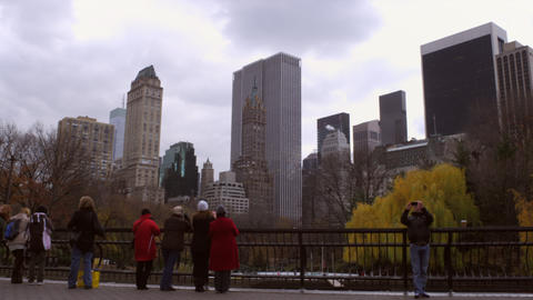 Tracking shot of onlookers and ice rink with city in background Footage