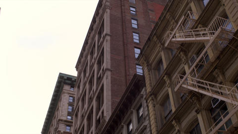 Dolly shot looking up at tall, old apartment buildings in New York City Footage