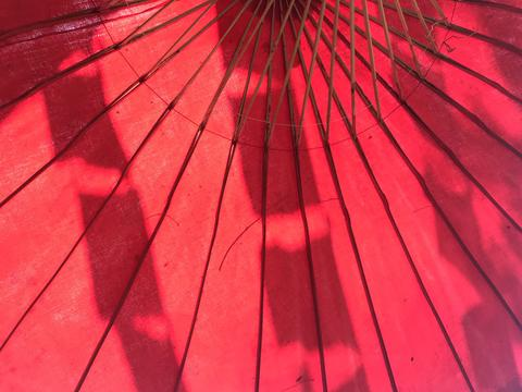 big red mulberry paper umbrella with rectangle flags shadow フォト