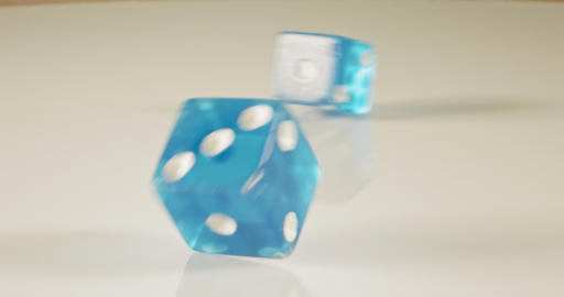Slow motion macro shot of dice falling and rolling on reflective surface Footage