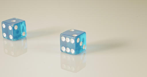 Slow motion macro shot of dice falling and rolling on reflective surface GIF