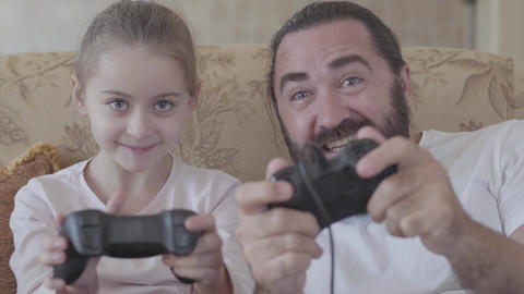 Portrait of a bearded dad and cute little daughter playing video games on gaming Footage