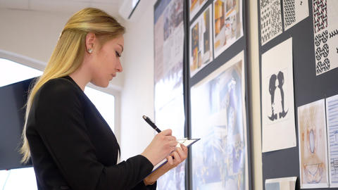 Young female designer checking the board and making notes GIF