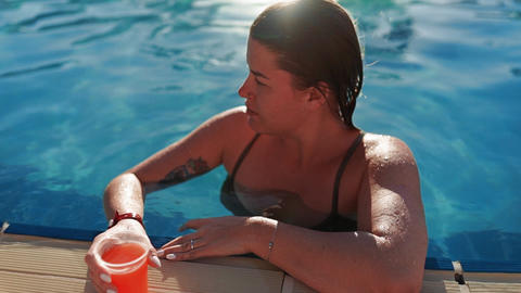 Woman swims to the edge of swimming pool, takes fresh juice, drinks it and swims Footage