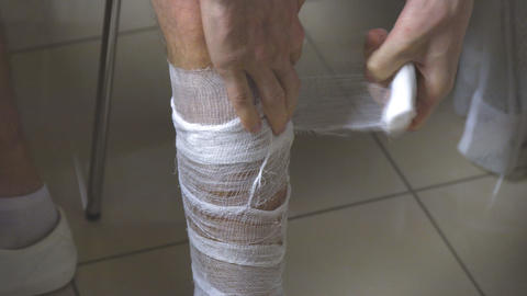 A man puts a bandage on his leg Footage