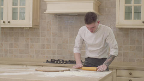 Rolling dough with rolling pin for pizza preparation on table. Chef rolling Live Action