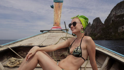 Happy woman traveler in bikini relaxing on boat Live Action