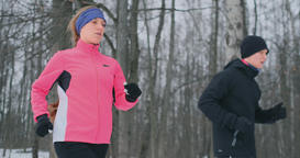 Young man and woman on a morning run in the winter forest. A woman in a loose Footage