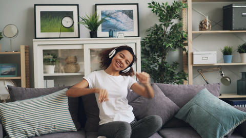Cute African American girl is listening to music using headphones, singing and Footage