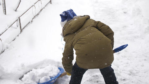 boy in christmas hat cleans snow with a shovel GIF