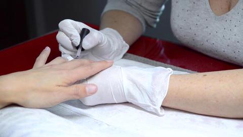 Close up shot of a beutician applying nail polish to female nail at nail salon Archivo