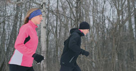 Young man and woman on a morning run in the winter forest. A woman in a loose Archivo