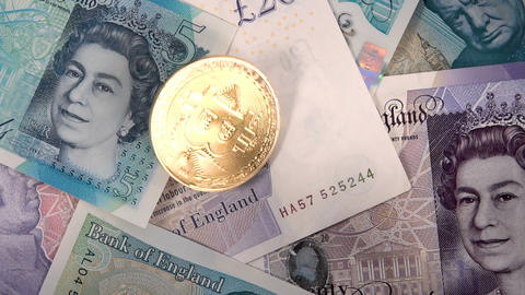 Single virtual cryptocurrency money Bitcoin golden coin on United Kingdom Pound sterling banknotes Footage