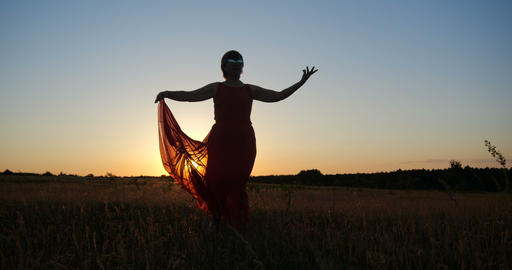 Inspired woman in a red dress dancing in a horizonless field at sunset Live Action